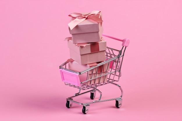 Mini Wózek Supermarketowy Z Pudełkami Prezentowymi Na Różowym Pastelowym Kolorze Premium Zdjęcia