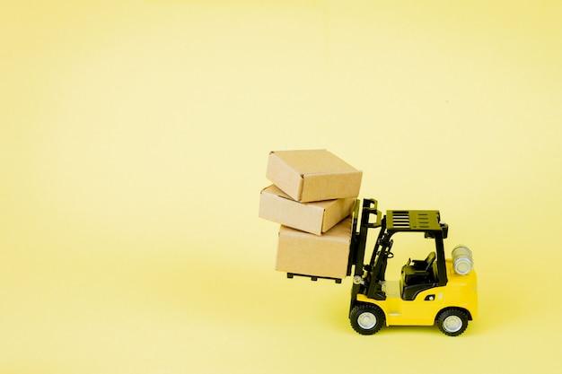 Mini wózek widłowy ładuje kartony. logistyka i pomysły na zarządzanie transportem oraz koncepcja handlowa przemysłu.