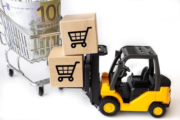Mini wózek widłowy ładuje kartony na zakupy do koszyka. przemysłowa koncepcja biznesowa i handlowa.