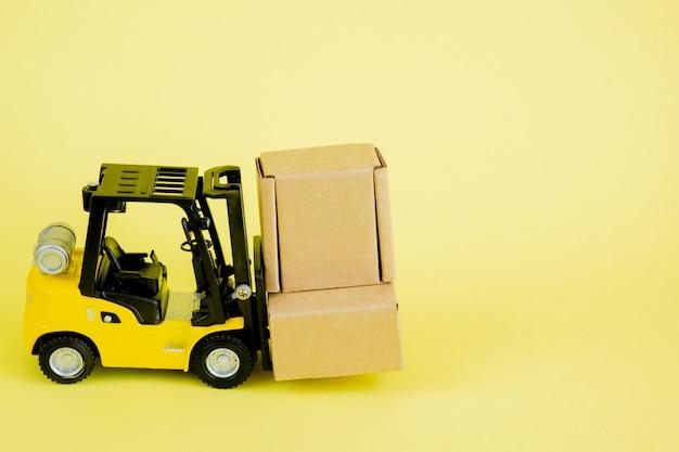 Mini wózek widłowy ładuje kartony. pomysły na zarządzanie logistyką i transportem oraz biznesowa koncepcja przemysłowa
