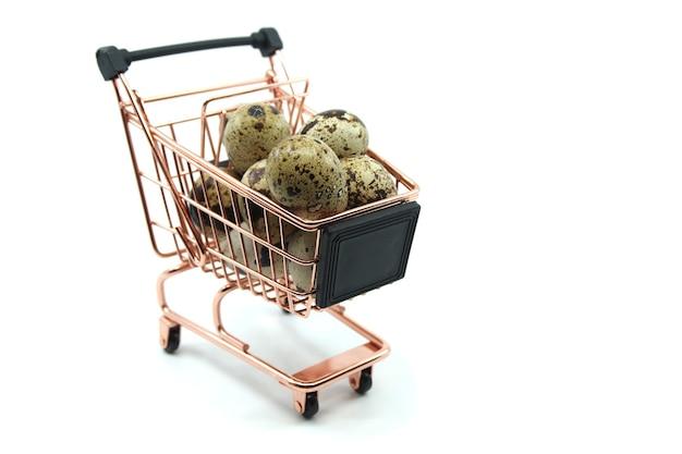 Mini wózek z jajami przepiórczymi na białym tle. zakupy i zakupy żywności koncepcja metafora.