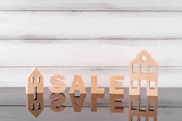Miniatura domu i napis sprzedażowy