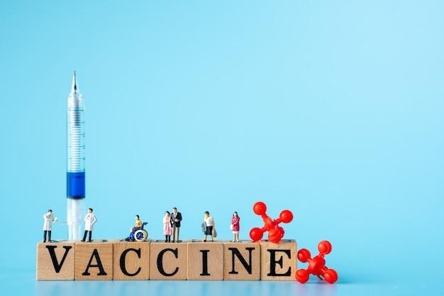"""Miniatura lekarza i pacjenta nosi maskę, aby zapobiec wirusowi. czerwony wirus z drewnianymi kostkami ze słowami """"szczepionka"""" i strzykawką."""