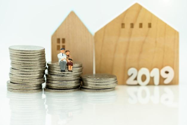 Miniatura starzy ludzie siedzi na monety stercie z domem