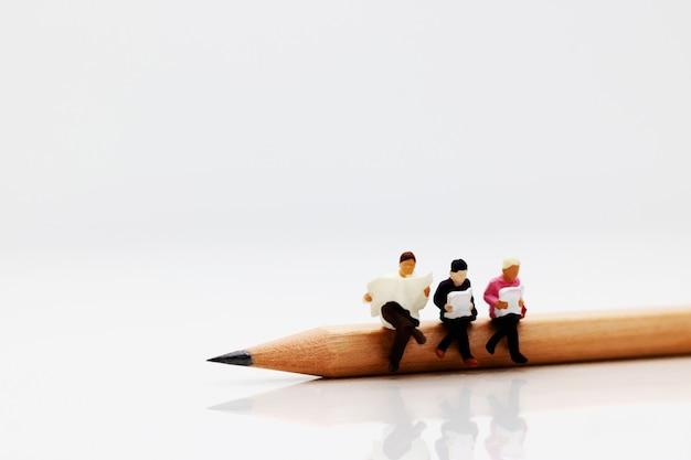 Miniaturowa biznes drużyna siedzi na ołówku i książce.