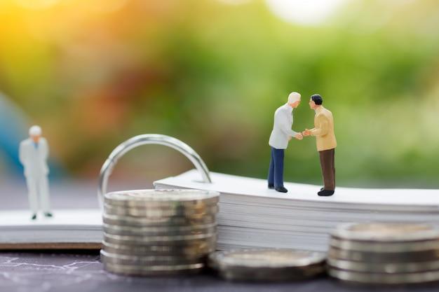 Miniaturowa biznesmen uścisk dłoni umowa na mapie z stertą monet.