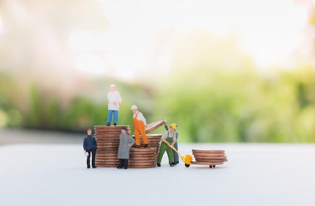 Miniaturowa biznesmena i pracownika pozycja na monetach i przewożenie monety