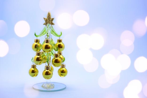 Miniaturowa choinka wykonana ze szkła ze złotymi kulkami na białym tle na tle reflektorów