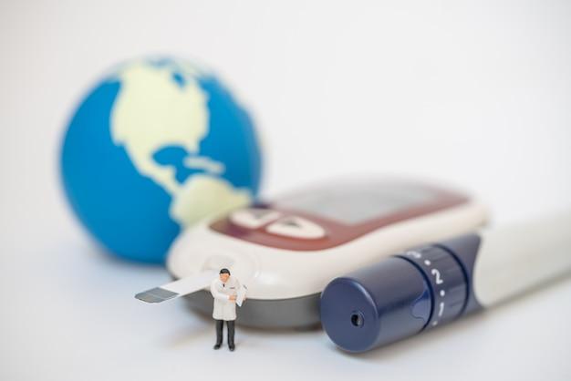 Miniaturowa figura lekarza z teczką pacjenta stojącą z lancetem, glukometrem i mini światową piłką, wykorzystującą jako koncepcję cukrzycy, glikemii, opieki zdrowotnej i ludzi.