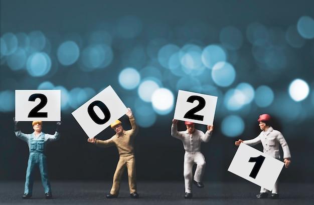 Miniaturowa figura pracowników pracowników trzymających i podnoszących numer 2021 dla koncepcji szczęśliwego nowego roku
