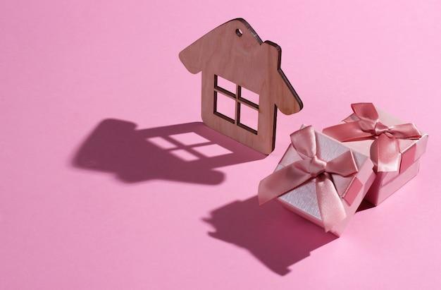 Miniaturowa figurka i pudełko na różowym pastelowym tle. studio strzałów z cieniem