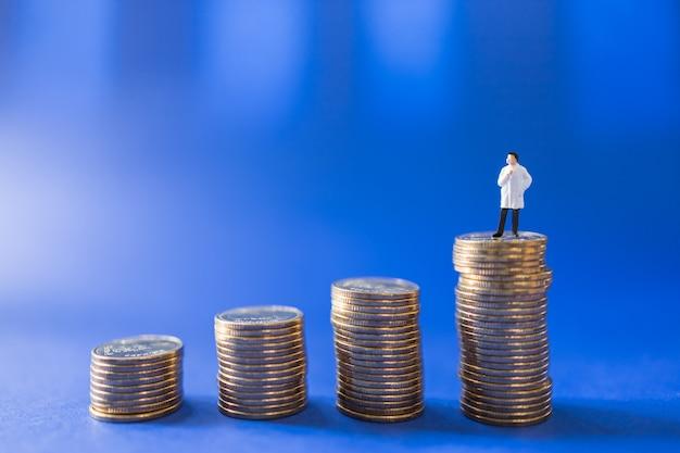 Miniaturowa figurka lekarza z maską stojącą na stosie złotych monet