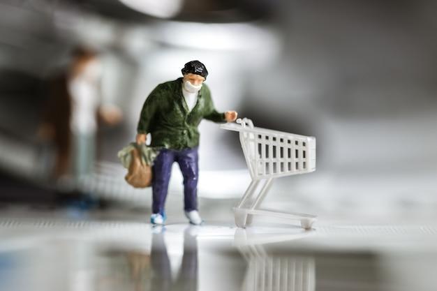 Miniaturowa figurka noszenia maski kupujący biznes popycha wózek na papierowy indeks ze stetoskopem
