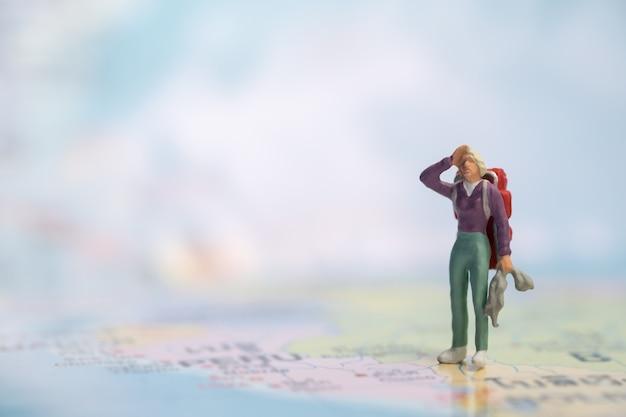 Miniaturowa figurka podróżniczki z plecakiem stojącym i spoczywającym na mapie świata.