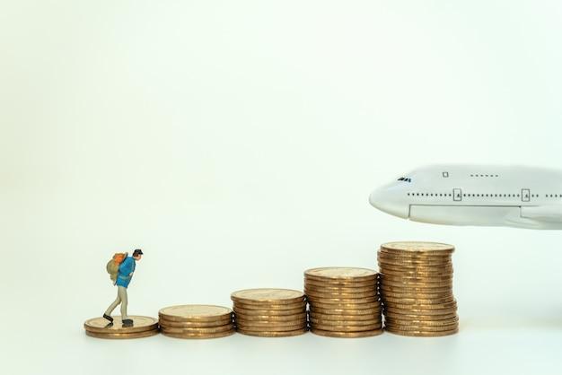 Miniaturowa figurka podróżnika z plecakiem idąca po stosie złotych monet do modelu mini samolotu