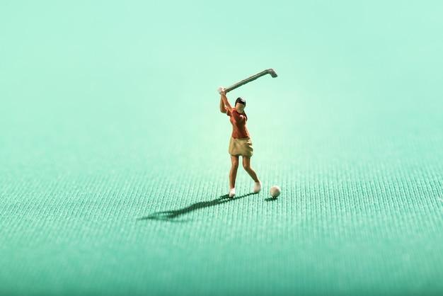 Miniaturowa kobieta bawić się golfa na zieleni