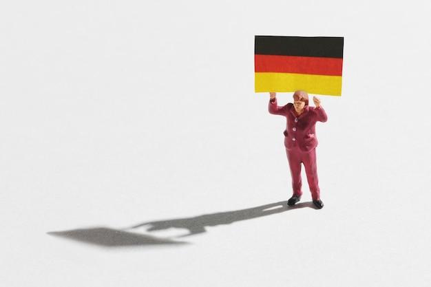 Miniaturowa kobieta z flagą niemiec