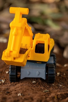 Miniaturowa koparka zabawkowa w kolorze żółtym i czarnym na ziemi z selektywnym skupieniem