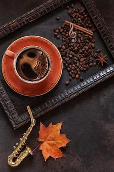 Miniaturowa kopia saksofonu, kawa, ziarna kawy i jasny wzór jesiennych liści