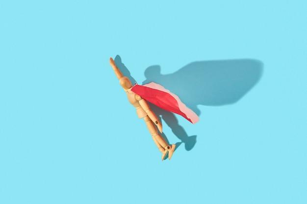 Miniaturowa lalka z drewnianego manekina w czerwonej pelerynie z podniesioną ręką leci w górę jako bohater