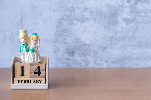 Miniaturowa para ślubna z drewnianym kalendarzem 14 lutego. walentynki