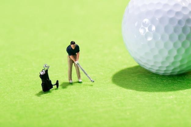 Miniaturowa postać golfisty wykonującego uderzenie
