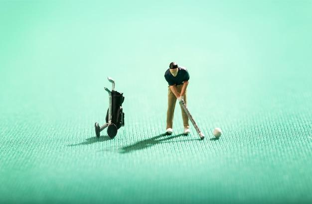 Miniaturowa postać mężczyzny grającego w golfa