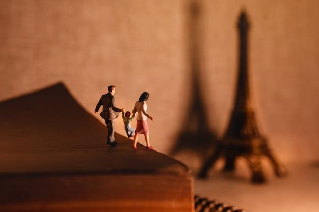 Miniaturowa rodzina turystyczna stojąca na wiekowej księdze.