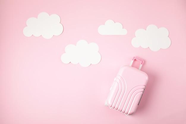 Miniaturowa różowa walizka nad różowym tłem