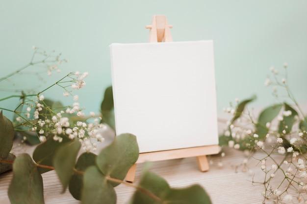 Miniaturowa sztaluga z pustym płótnem ozdobionym liśćmi i kwiatami oddechu dziecka na pastelowym tle