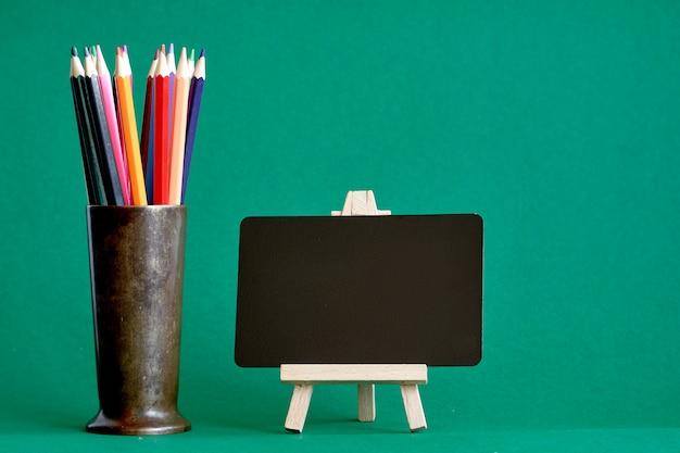 Miniaturowa tablica kredowa na sztaludze i wielokolorowe ołówki w metalowym stojaku, koncepcja powrót do szkoły