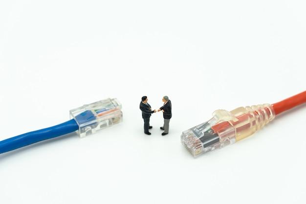 Miniaturowe 2-osobowe biznesmeni uścisnąć dłoń na plecach negocjowanie w biznesie.