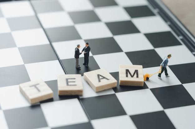 Miniaturowe biznesmenów 2 osób uścisnąć dłoń na szachownicy