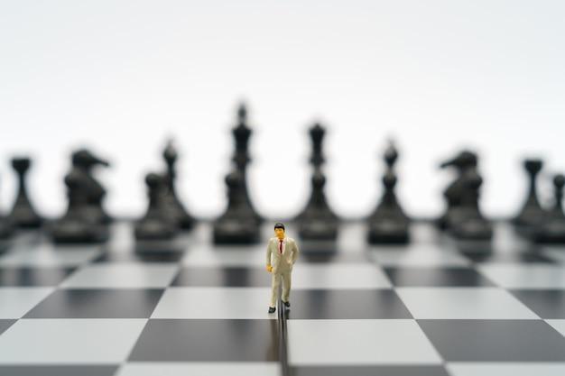 Miniaturowe biznesmenów 2 osoby stojące na szachownicy z bierką szachową