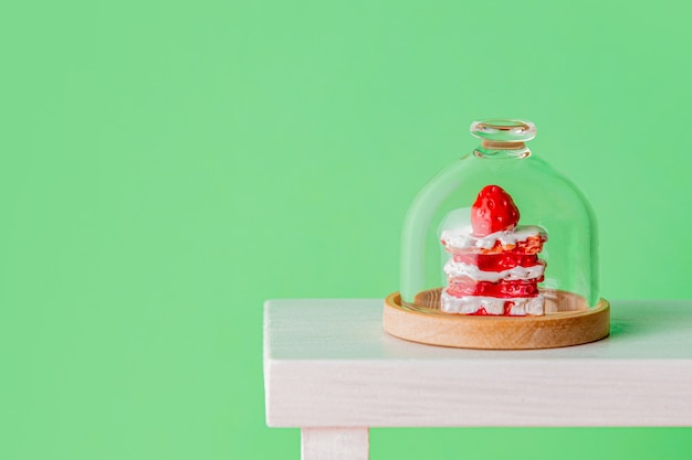 Miniaturowe ciasto pod szkłem na zielonym tle
