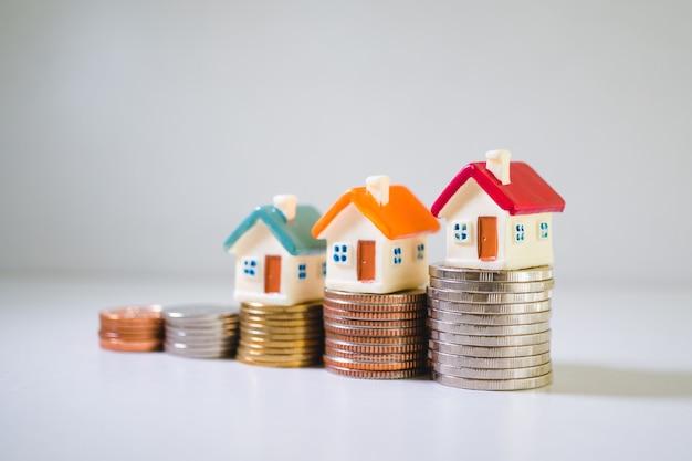 Miniaturowe domy na stosie monet