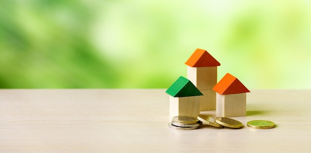 Miniaturowe drewniane domy i monety na drewnianym stole i zielonym tle przyrody - inwestycje w nieruchomości, drabina nieruchomości, koncepcja hipoteki.