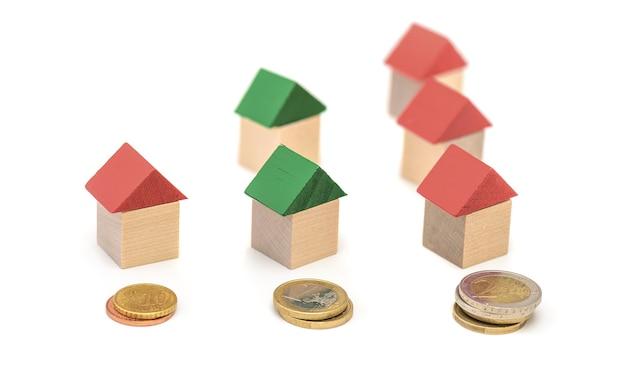 Miniaturowe drewniane domy i stosy monet - drabina nieruchomości, koncepcja inwestycji hipotecznych i nieruchomości.
