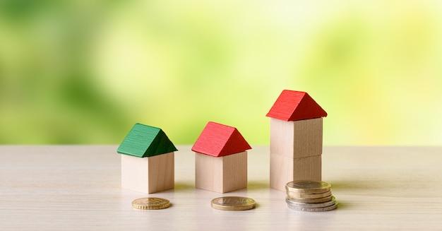 Miniaturowe drewniane domy i stosy monet na drewnianym stole i zielonym tle przyrody - inwestycje w nieruchomości, drabina nieruchomości, koncepcja hipoteki.