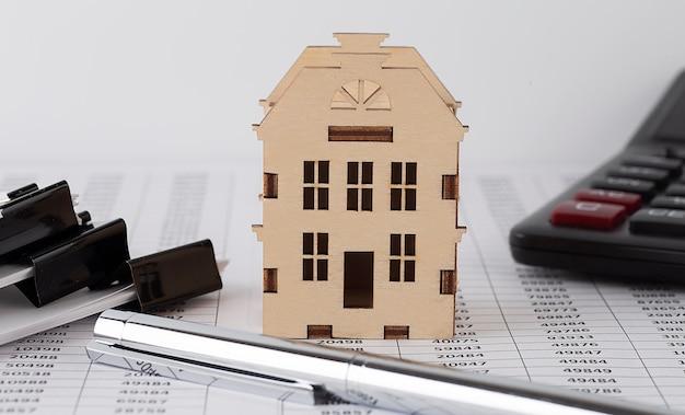 Miniaturowe drewniane domy i wykres, kalkulator. nieruchomość.