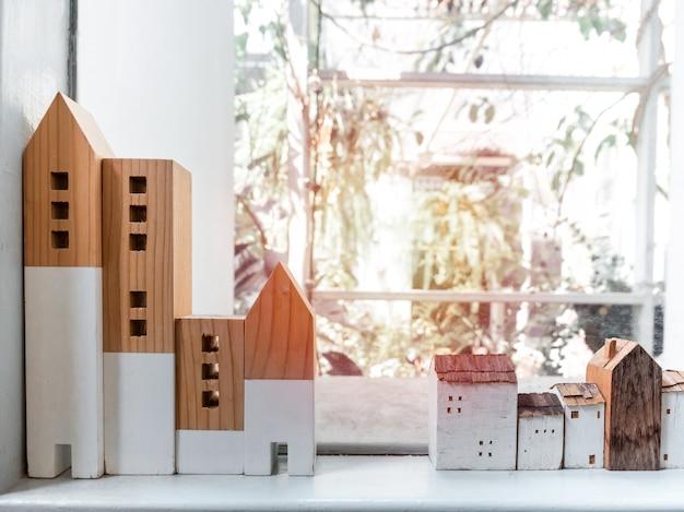 Miniaturowe drewniane domy na białej półce w pobliżu szyby z promieni słonecznych.