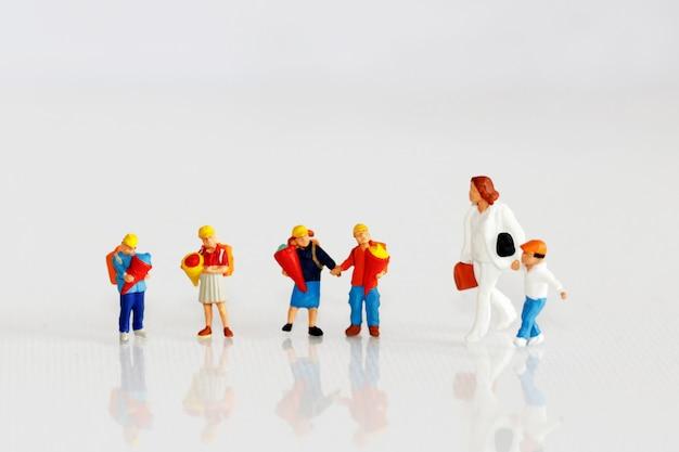 Miniaturowe dzieci z plecakiem idą do szkoły.