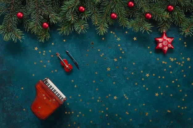 Miniaturowe kopie fortepianu i skrzypiec z świątecznym wystrojem i brokatem.