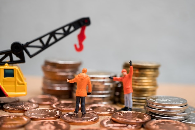 Miniaturowe ludzi, inżynierów pracujących z dźwigiem pojazdu na stos monet