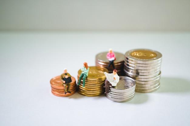 Miniaturowe ludzi siedzących na stosie monet