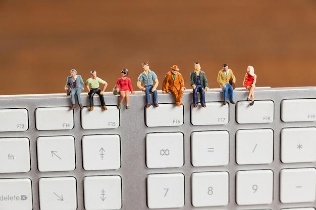 Miniaturowe ludzi siedzi na górze klawiatury