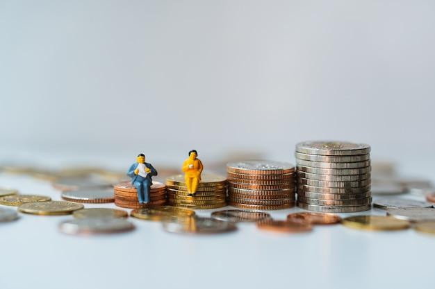 Miniaturowe ludzie, mężczyzna i kobieta siedzi na stosie monet za pomocą koncepcji biznesowej i finansowej