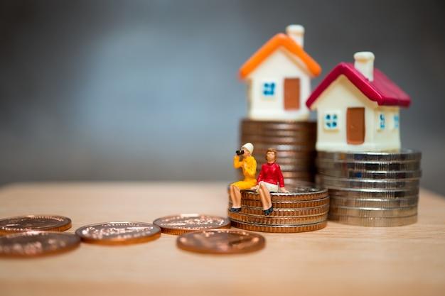 Miniaturowe ludzie, para kobieta siedzi na monety stosu i mini domu