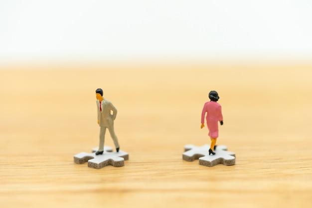 Miniaturowe ludzie przedsiębiorców stojących na białym jigsaw