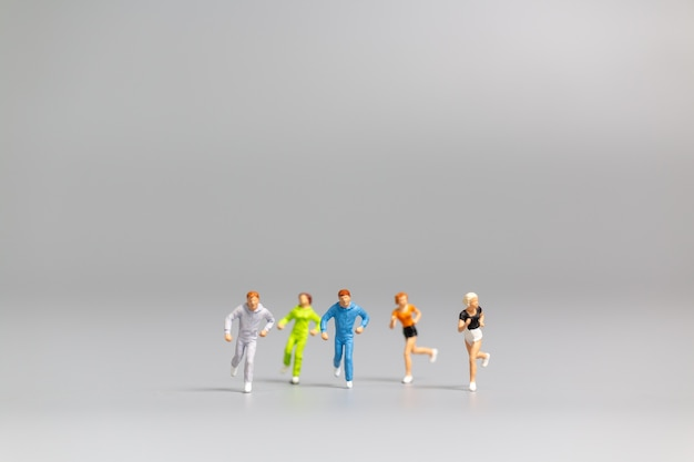 Miniaturowe osoby biegające na szarym tle i wolne miejsce na tekst